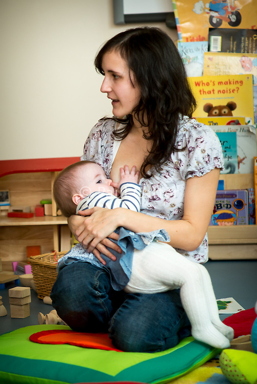 A mother breastfeeding her baby at a drop-in breastfeeding support centre while talking to another mother.<br /> <br /> Image from the &quot;We Do It In Public&quot; documentary photography project collection: <br />  www.breastfeedinginpublic.co.uk<br /> <br /> Dorset, England, UK<br /> 17/04/2013