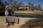 A local Siwan young man dressed in traditional clothing sits next to Cleopatra's Bath, a natural and warm spring in Siwa Town of the Siwa Oasis, Egypt.