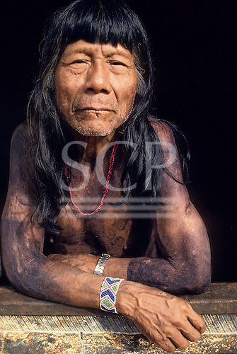 A-Ukre Village, Xingu, Brazil. Tikiri, an elder of the village, with black Genipapo body paint, bead bracelet and watch.