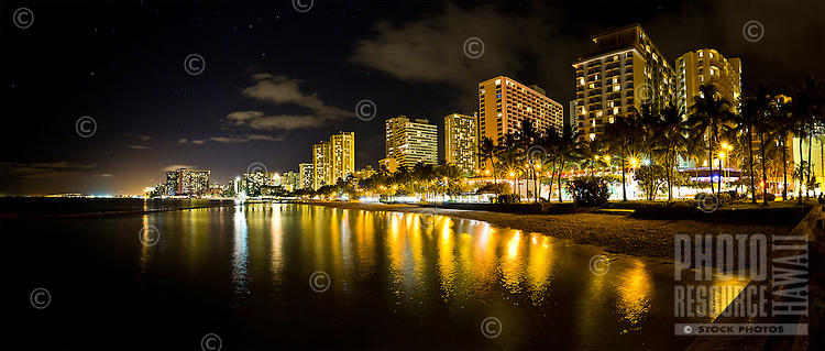 Waikiki's city lights are reflected in the calm waters along the shore of one of its beaches, Honolulu, O'ahu.