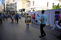 A man walks down Istiklal Street, the main pedestrian thoroughfare of Beyoglu, carrying a painting of Mustafa Kemal Ataturk, the father of the Turkish Republic, in Istanbul, Turkey on May 8, 2012.