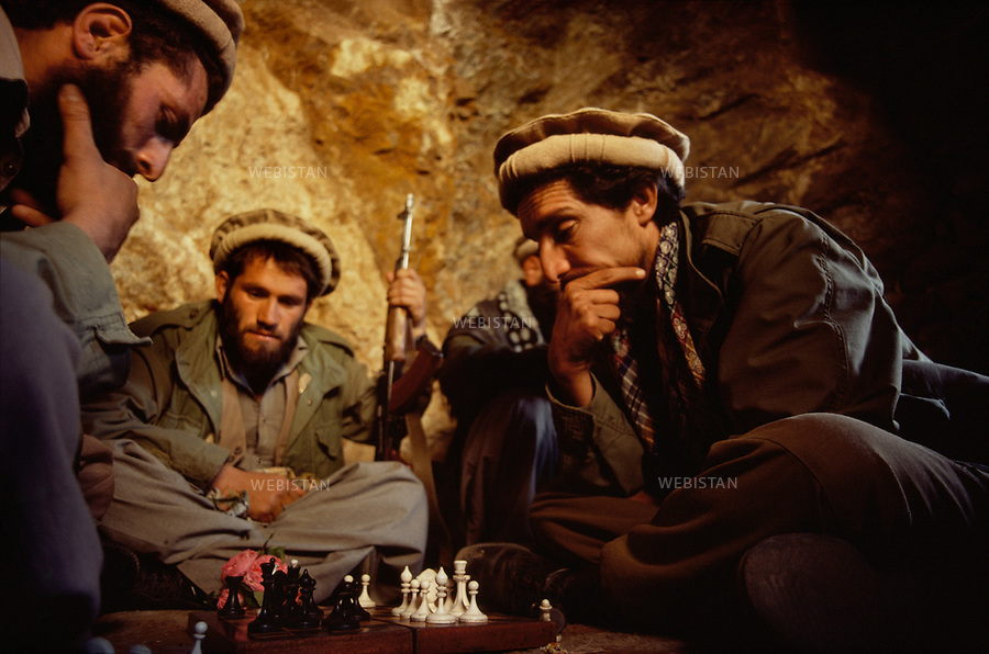 Afghanistan. Panjshir Valley. 1985. Commander Massoud (1953-2001) plays chess with a group of Mujahideen during the Soviet invasion of Afghanistan (1979-1989). <br /> <br /> Afghanistan. Vall&eacute;e du Panjshir. 1985. Le commandant Massoud (1953-2001) joue aux &eacute;checs avec un groupe de Moudjahidin pendant la guerre d'Afghanistan (1979-1989).