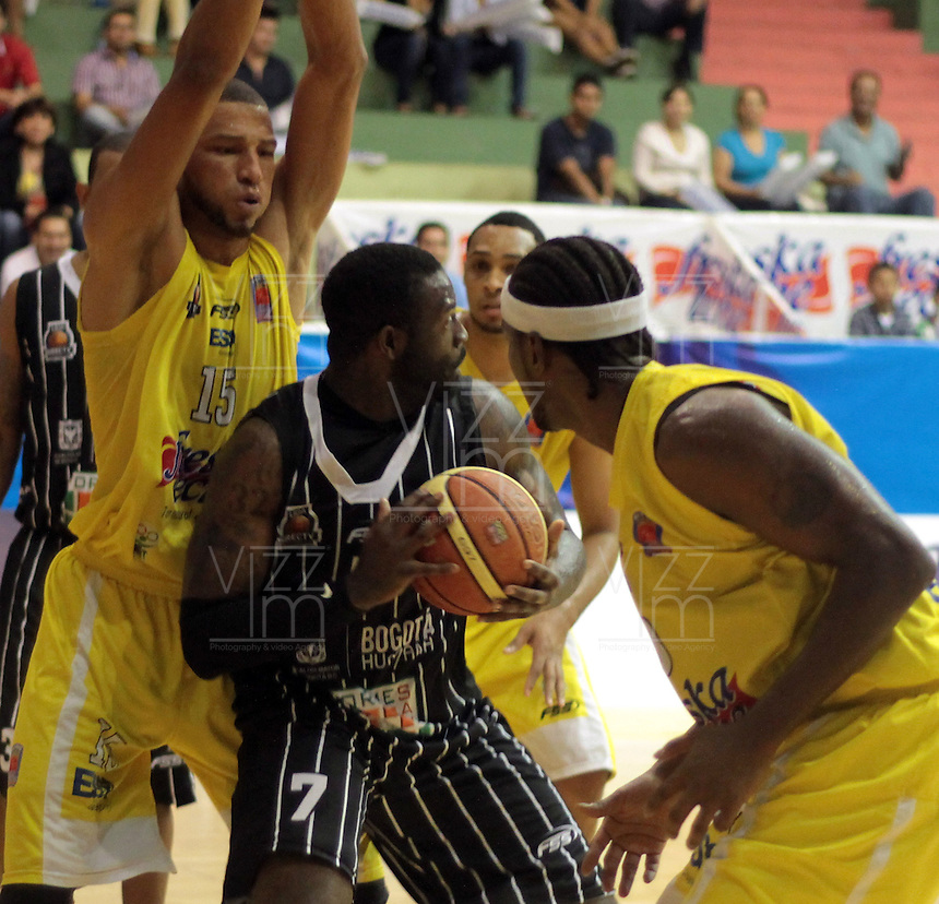 BUCARAMANGA -COLOMBIA, 17-05-2013. Hernández Villamil (I) y Jason Edwin (D) de Búcaros disputa el balón con Jeff Jahnbulleh (c) de Piratas durante partido de la fecha 17 fase II de la  Liga DirecTV de baloncesto Profesional de Colombia realizado en el Coliseo Vicente Díaz Romero de Bucaramanga./  Hernández Villamil (L) and Jason Edwin (R) of Bucaros fights for the ball with Piratas player Jeff Jahnbulleh (C) during match of the 17th date phase II of  DirecTV professional basketball League in Colombia at Vicente Diaz Romero coliseum in Bucaramanga. Photo:VizzorImage / Jaime Moreno / STR