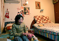 11 year old Liu Fangyuan (Yuan Yuan) sits on her bed in the bedroom that she shares with her parents in Nanjing, China. In 2002, Yuan Yuan's aunt poured sulfuric acid on her face after losing a housing dispute with Yuan Yuan's father, The attack blinded and seriously disfigured Yuan Yuan, while her aunt is serving a life sentence in prison, Yuan Yuan and her family awaits a controversial face transplant...PHOTO BY SHEN / SINOPIX