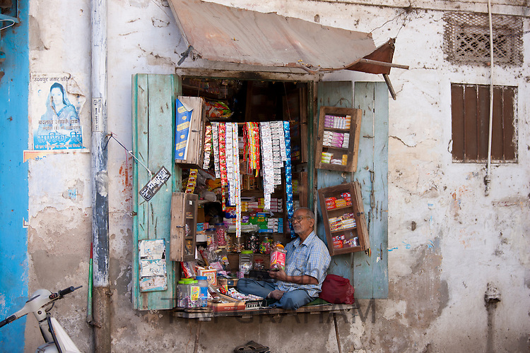 Stallholder selling sweets, tobacco and foods sits in shop window in old town in Udaipur, Rajasthan, Western India