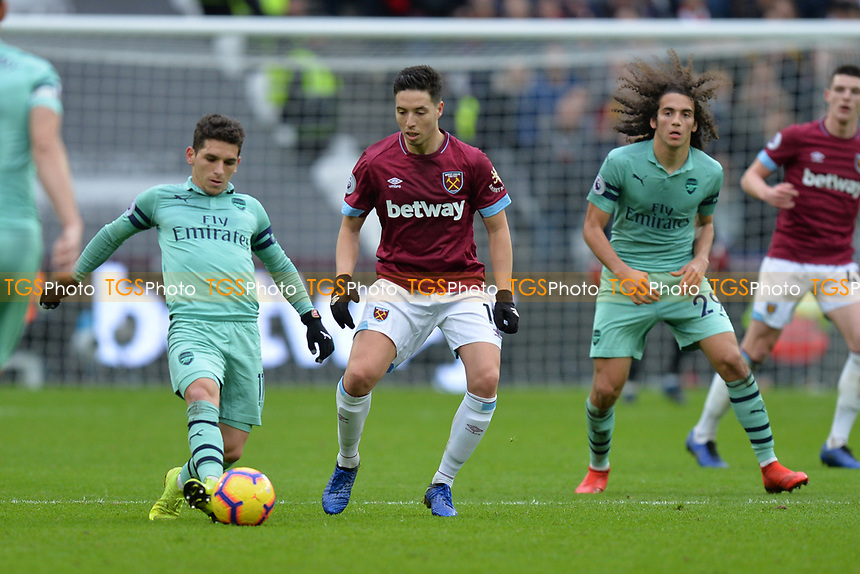 Samir Nasri of West Ham United and Lucas Torreira of Arsenal during West Ham United vs Arsenal, Premier League Football at The London Stadium on 12th January 2019
