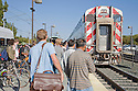 Commuters waiting to board the northbound Caltrain train during the afternoon rush hour. Mountain View, California, USA