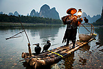 China, Guangxi Zhuangzu Zizhiqu, Guangxi, Yangshuo, Cormorant fisherman with karst mountains and Li River in the background