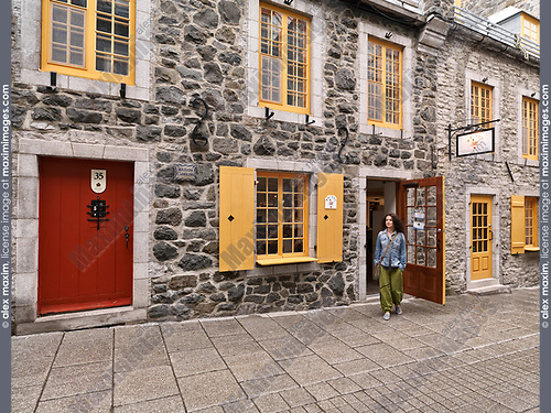 Young woman in front of the Amimoc Native American shoe store on Rue Petit Champlain historic street in Old Quebec City at daytime, Canada. Rue du Petit-Champlain, Ville de Québec.