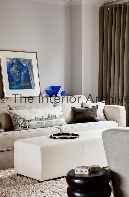 An informal living room with a sofa and ottoman upholstered in neutral fabrics. Blue glassware and a painting are displayed on a shelf behind the sofa giving a spot of contrasting colour.