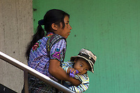 A woman struggles to lift her child on some stairs at  Santiago Atitlan in Guatemala.