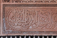 Kufic calligraphy in stucco from courtyard of Ben Youssef Madrasa, Medina, Marrakech, Morocco. This inscription is carved in Iraqi kufic style interwoven with a vegetal design. The Madrasa is an Islamic theological college founded in the 14th century and rebuilt by the Saadians in the 1560s. It is named after the Almoravid Sultan Ali ibn Yusuf, who reigned 1106-42. Picture by Manuel Cohen