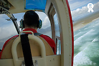 Male pilot wearing headset, flying helicopter, rear view (Licence this image exclusively with Getty: http://www.gettyimages.com/detail/200503178-001 )