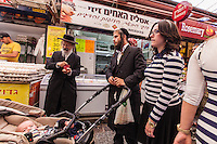 Israel,Jerusalem, an orhodox jude family is choosing the food for Shabbat in   the Mahane Yehuda Open Air Food Market,