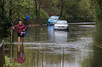 Pictured: A woman is seen walking through the water where a Vauxhall Astra convertible is stranded on the B4242 road between Resolven and Glyn Neath in south Wales, UK. Saturday 13 October 2018<br /> Re: Flooding caused by Storm Callum in the Neath area, south Wales, UK.