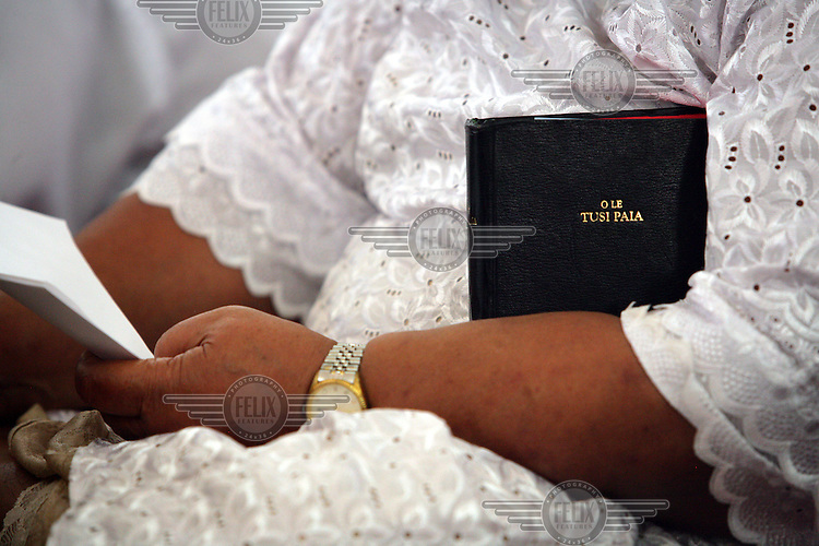 A woman holds a Samoan bible during a chuch service in Apia Cathedral. Samoa (formerly known as Western Samoa).