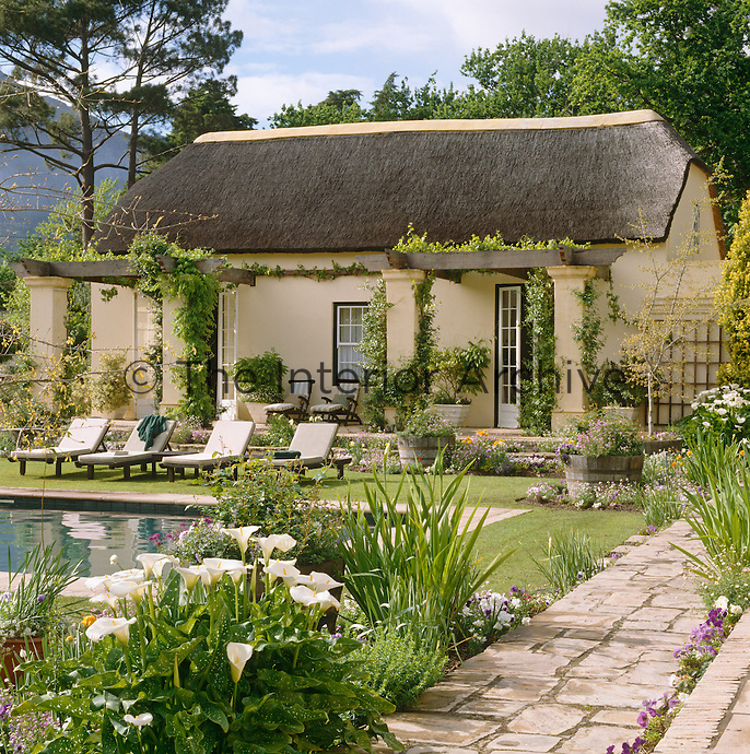 The guest wing with a thatched roof faces the swimming pool across a garden of blue and white flowers
