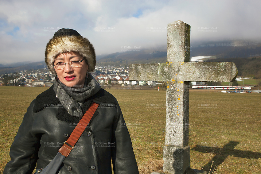 Switzerland. Canton Solothurn. Olten. Dolma Knell enjoys walking outside near her home. A protestant Christian cross depicting the cross without the corpus and a SBB CFF Intercity train. The swiss tibetan woman is an Aeschimann's child who arrived 50 years ago in Switzerland to receive custody on a private initiative by an influential Swiss industrialist, Charles Aeschimann. In 1962, Charles Aeschimann agreed with the Dalai Lama to take 200 children and place them in Swiss foster homes and give them a chance for a better life and a good education. Most of the children still had parents in exile or in Tibet, just a few were orphans. 25.02.2015 © 2015 Didier Ruef