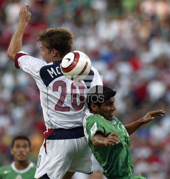 USA's Brian McBride, goes up for a header over Mexico's Carlos Salcido, right.