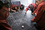 Monks working to recreate a sand-mandala, they now have a barrack like temporary building as a tempel. Yushu.