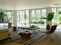 In the living room a reading area is defined by a striped rug and tasteful designer seats