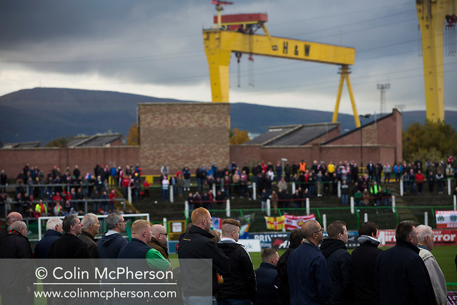 Home and away supporters watching the first-half action at The Oval, Belfast as Glentoran (in green) host city-rivals Cliftonville in an NIFL Premiership match. Glentoran, formed in 1892, have been based at The Oval since their formation and are historically one of Northern Ireland's 'big two' football clubs. They had an unprecendentally bad start to the 2016-17 league campaign, but came from behind to win this fixture 2-1, watched by a crowd of 1872.
