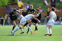 Alex Goode of Saracens is dumped tackled as Owen Farrell and George Kruis of Saracens get caught up in the action