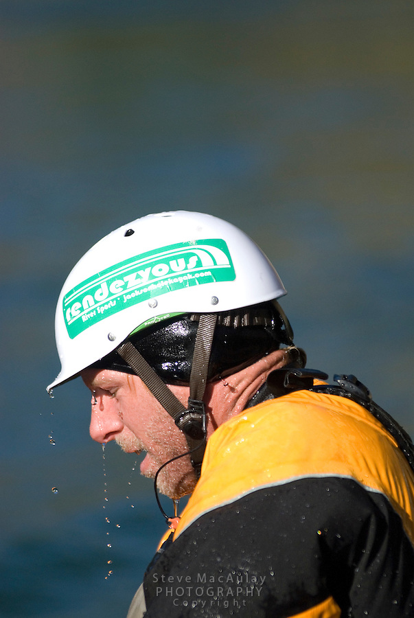 Water streaming off helmet and nose of male whitewater kayaker in yellow paddle jacket, white helmet, Snake River, Jackson,  Wyoming.