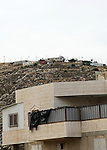 A picture taken on May 17, 2013 shows a house belonging to Palestinians in front of houses in the Mitzpe Lachish Israeli settlement outpost (background) in the West Bank village of Beit Awwa. Israeli settlement watchdog Peace Now said on May 16, 2013 that the government wants to give retroactive approval to four West Bank settlement outposts it had previously pledged to at least partially demolish. Givat Assaf, Givat HaRoeh, Maaleh Rehavam and Mitzpe Lachish outposts are among six listed in a 2005 government report as deserving immediate eviction and later ordered shut by a court order. Photo by Mamoun Wazwaz
