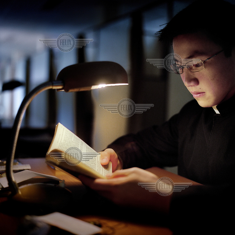19 year old Samuel Chow studies using the light of a lamp at the Legionaries of Christ seminary in Salamanca. Samuel was born in Canada and entered the seminary when he was 11 years old. The Legion of Christ is a conservative Roman Catholic congregation whose members take vows of chastity, obedience and poverty.