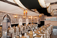 The large restaurant tent is decorated with rich textiles hanging from the ceiling and intimate table lanterns