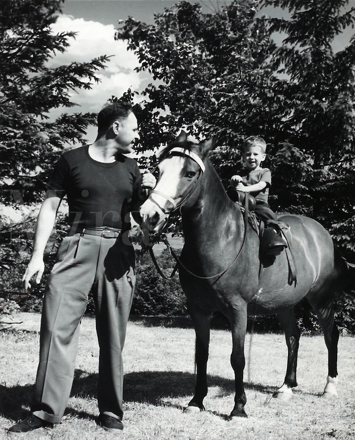 Man leading horse with young son riding bareback. 1950's.