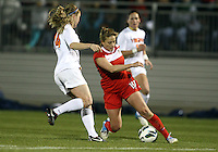 BOYDS, MARYLAND - April 06, 2013:  Caroline Miller (10) of The Washington Spirit cuts over Kristen McNabb (14) of the University of Virginia women's soccer team in a NWSL (National Women's Soccer League) pre season exhibition game at Maryland Soccerplex in Boyds, Maryland on April 06. Virginia won 6-3.