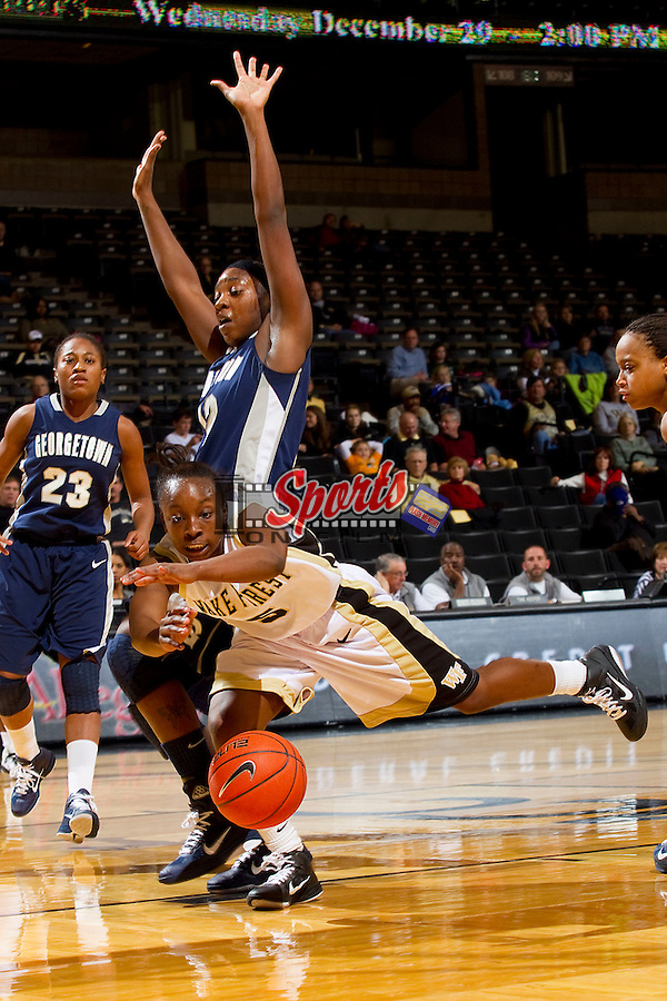 Chelsea Douglas #5 of the Wake Forest Demon Deacons loses the ball as she drives to the basket past Tommacina Mcbride #12 of the Georgetown Hoyas at the Lawrence Joel Coliseum on December 4, 2010 in Winston-Salem, North Carolina.  Photo by Brian Westerholt / Sports On Film