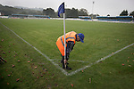 A volunteer collecting a corner flag at the Harry Williams Riverside Stadium at the conclusion of the Northern Premier League premier division match between Ramsbottom United and Barwell. This was the club's 13th league game of the season and they were still to record their first victory following a 3-1 defeat, watched by a crowd of 176. Rams bottom United were formed by Harry Williams, the current chairman, in 1966 and progressed from local amateur football  in Bury to the semi-professional leagues.