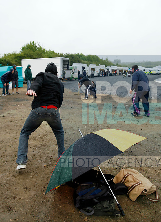 Fans play a game of cricket despite the bad weather