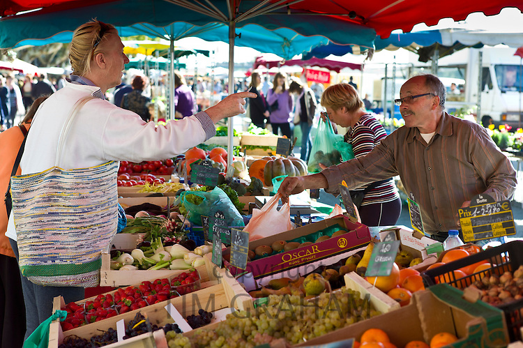 Frenchman serving customer at fruit staff at food market at Esplanade  des Quais in La Reole, Bordeaux region, France