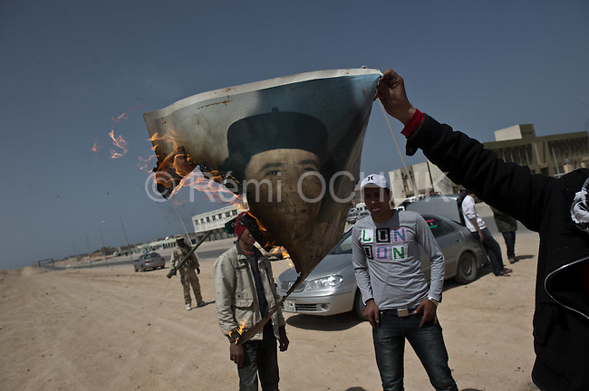 © Remi OCHLIK/IP3 - Bin Jawaad March 27, 2011 - Libyan fighters celebrate as they just took back the city of Bin Jawaad without fighting, they found the city empty from the loyalist Khadafi forces - They burn Khaddafi portrait and the green flag