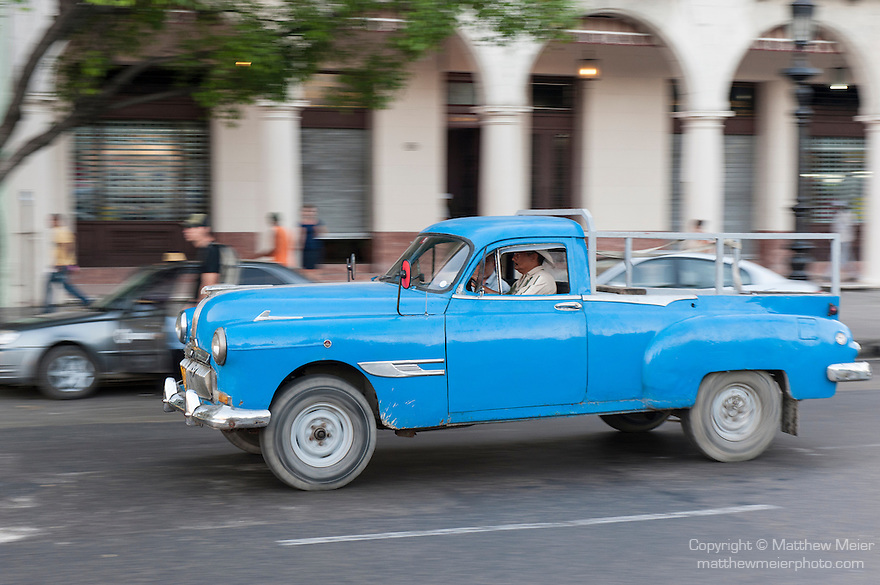 Havana, Cuba; a classic teal blue 1949 Pontiac modified pickup truck driving down the Paseo de Marti in Old Havana