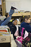 Oakland CA African American 2nd grader having trouble sitting  straight in chair in class