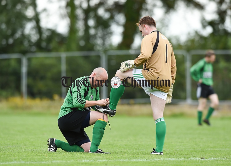 Sean O Regan of Treaty Celtic ties the boot lace of team mate and goalie Shane Thornton during their game against Rhine Rovers at Lees Road. Photograph by John Kelly.