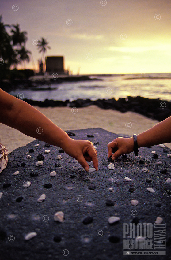 two women playing konane, Hawaiian checkers, at Puu honua honaunau, city of refuge, a national historical park on the Big island of Hawaii