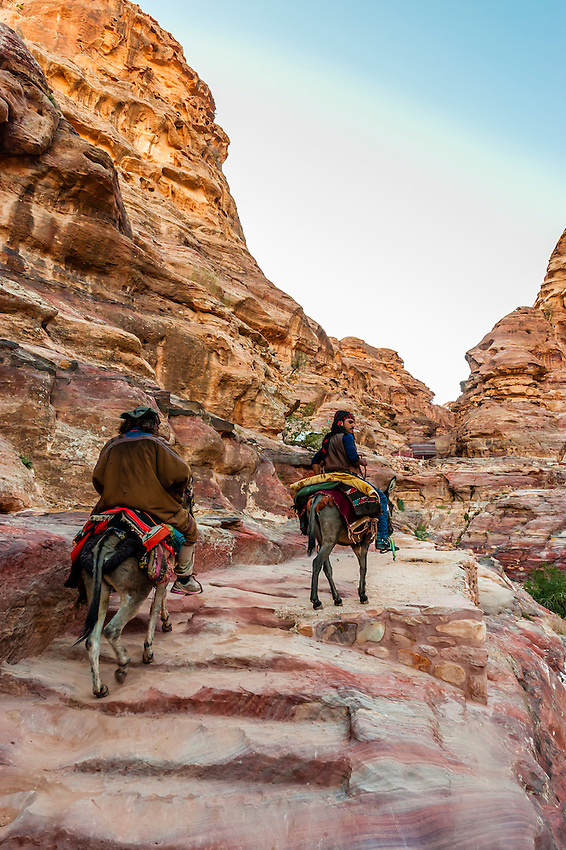 Bedouin men on donkeys, climbing the 800 steps that lead to The Monastery monument, Petra Archaeological Park (a UNESCO World Heritage Site), Petra, Jordan.