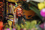Bao-jhong Yi-min Temple, Kaohsiung --The main god statue at the temple framed by blooming orchids.