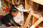 Education preschool 2-4 year olds girl and boy playing in block area using blocks as ramps horizontal