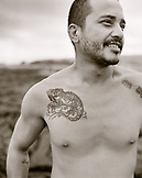 USA, Hawaii, The Big Island, smiling fisherman with a tattoo on chest at Puna Lu'u Beach (B&W)