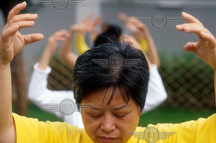 A Falun Gong follower assumes a sitting position during a meditation session in Hong Kong's Victoria Park.  Also known as Falun Dafa, the practice of Falun Gong involves a series of five meditaiton exercises to achieve a higher moral awareness.  The movement has proved particularly controversial since it was suppressed by the Chinese government on account of its alleged illegal activities.  Practitioners of Falun Gong claim that the Chinese government and police force has committed human rights abuses against the group in an attempt to marginalise the movement...