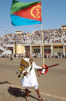 Eritrea. Asmara. September square. Meskel is the most important religious feast for the orthodox church in Eritrea. It takes place every year on september 27.An old bald man dresed as an antique warrior holds a sword in one hand and in the other a platic shield and a eritrean flag on a pole.  The public is seated on the terraces. © 2002 Didier Ruef