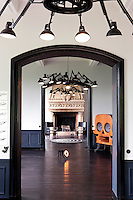 "Black-framed doorways create an enfilade through adjoining rooms towards a massive stone fireplace, each room punctuated by a ""Dear Ingo"" pendant light by Ron Gilad"
