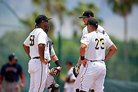 GCL Pirates pitching coach Fernando Nieve (59) talks with pitcher Jake Sweeney (65), catcher Daniel Angulo (27), and first baseman Kaleb Foster (23) during a Gulf Coast League game against the GCL Red Sox on August 1, 2019 at Pirate City in Bradenton, Florida.  GCL Red Sox defeated the GCL Pirates 11-3.  (Mike Janes/Four Seam Images)